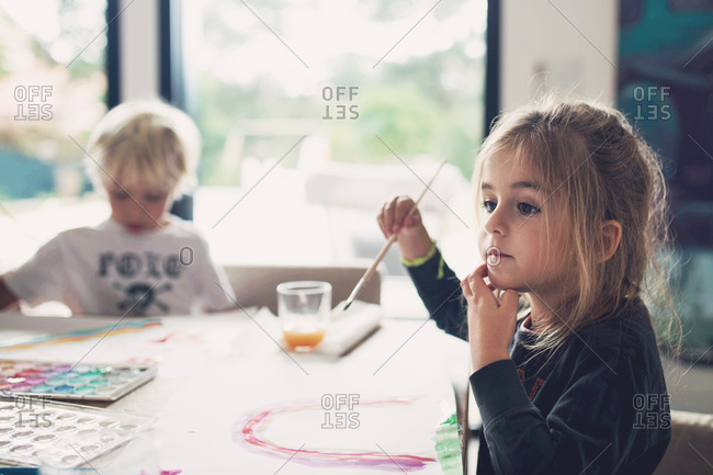 Children painting pictures at a table