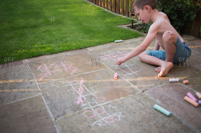 Boy drawing tic tac toe boards on sidewalk with chalk