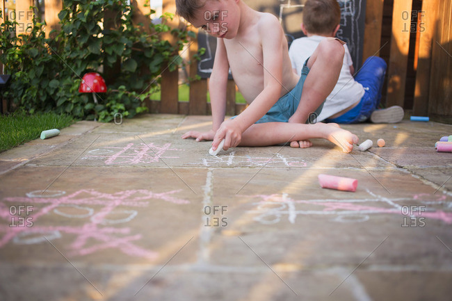 Low angle view of children drawing with sidewalk chalk