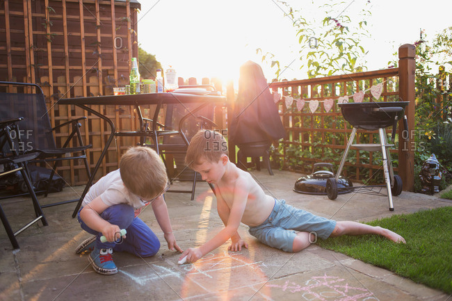 Boys playing tic tac toe on walkway with chalk at dusk