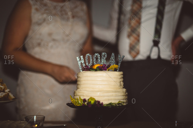 Close-up of wedding cake with bride and groom in background