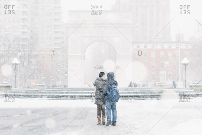 Tourists photographing Washington Square Arch during a snowstorm, New York City