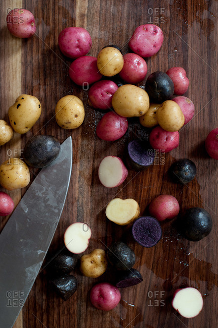 Multiple colored potatoes on a cutting board
