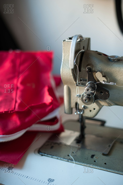 Red fabric sits next to an industrial sewing machine