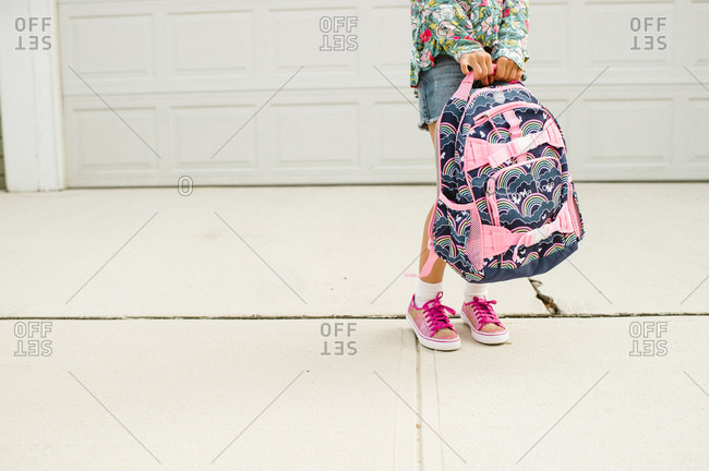 Young girl holding her backpack