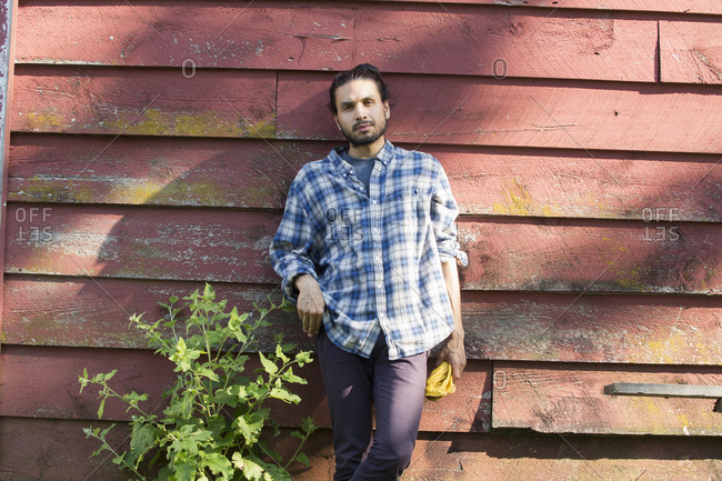 Bearded man wearing a checkered shirt leaning against a wooden wall in the shade