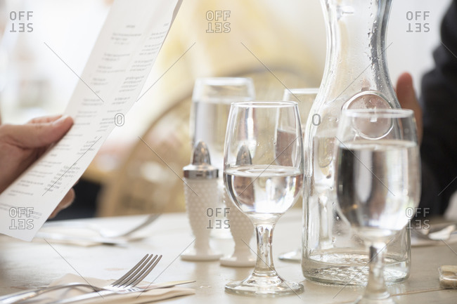 Close up of wine and water glasses and place settings at a table in a restaurant