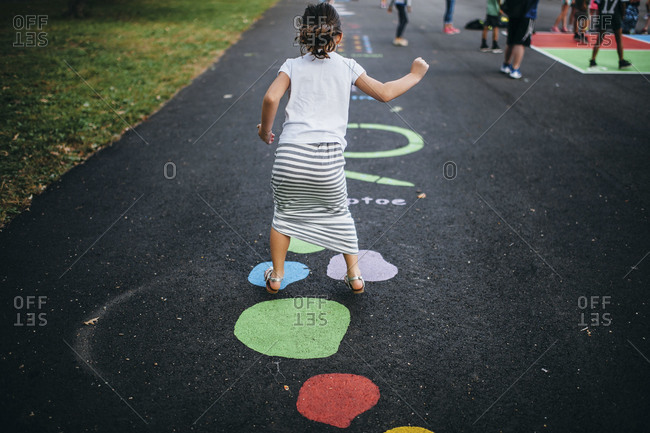 A young girl plays floor game in a park