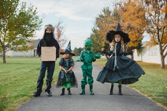 Four kids in Halloween costumes on neighborhood sidewalk
