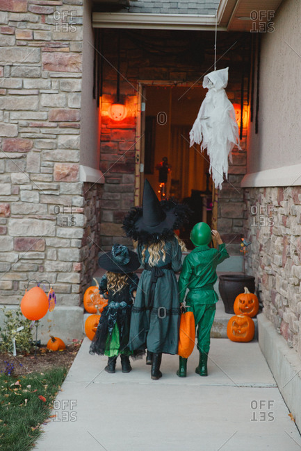 Three kids in costumes at a front door