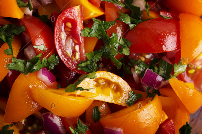 Overhead view of red and orange tomato salad with basil and onion
