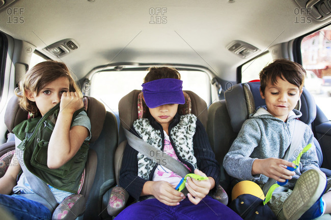 Three children strapped in car seats across the back seat of vehicle
