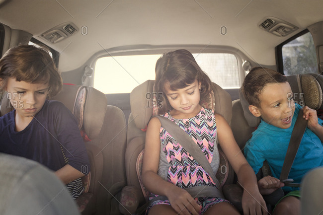 Children in child seats riding in a car