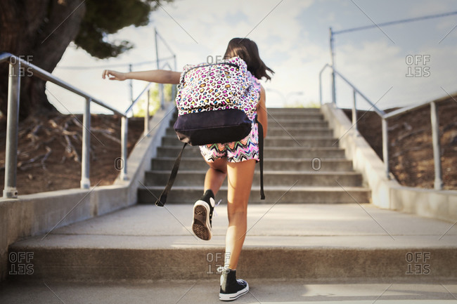 Girl with a backpack running up stairs