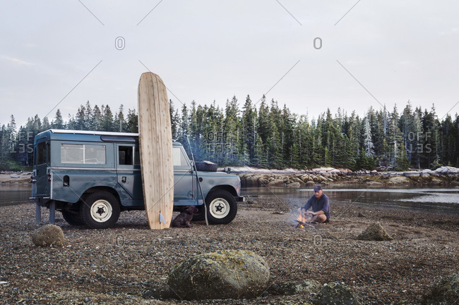 Man resting on lake beach near dog and vehicle
