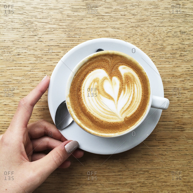 Hand of a woman holding a cup of cappuccino