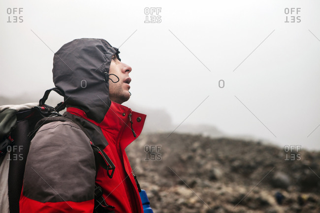 Hiker with his hood up in inclement weather