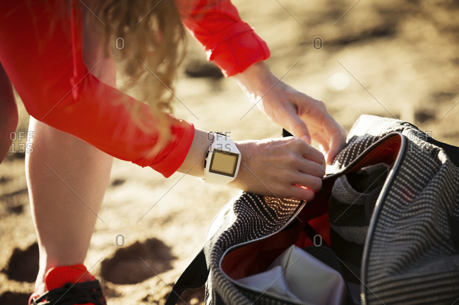 Female athlete with fitness tracker looking in bag