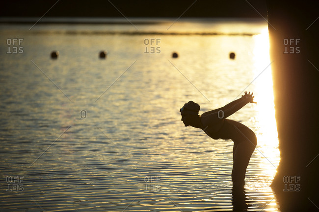 Silhouette of female swimmer stretching by lake