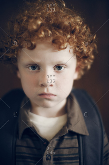 Portrait of ginger boy with backpack in school