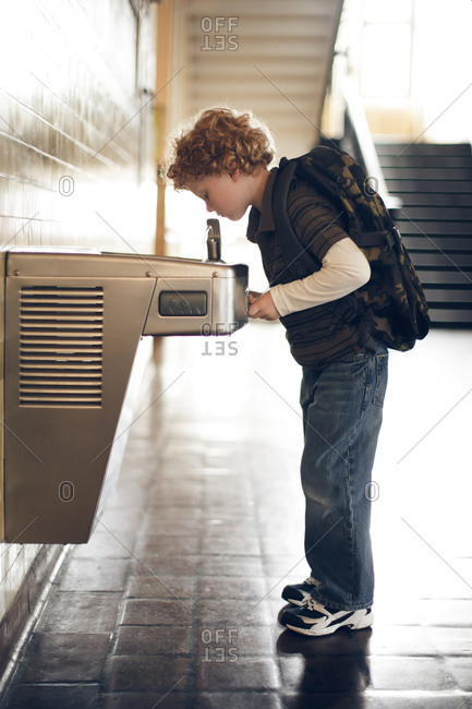 Boy wearing backpack at school drinking fountain
