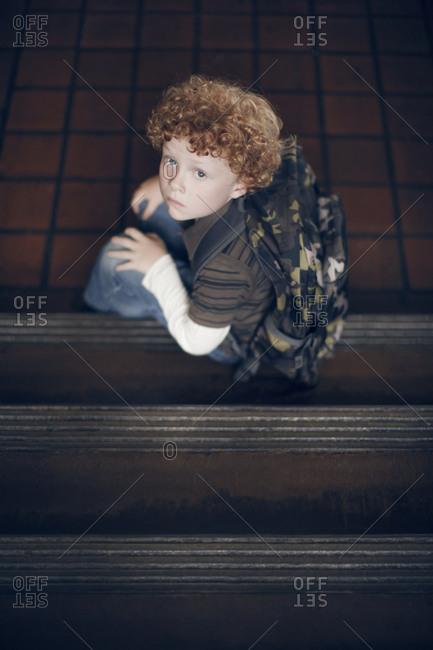 Boy sitting at base of steps in school