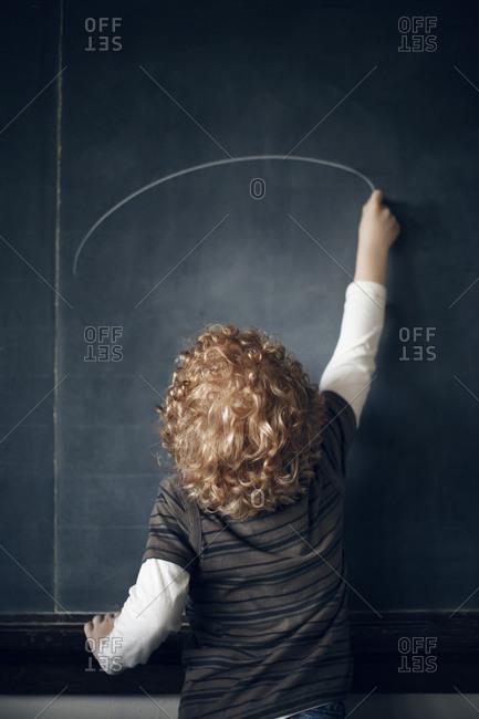 Boy drawing on a chalkboard in a school
