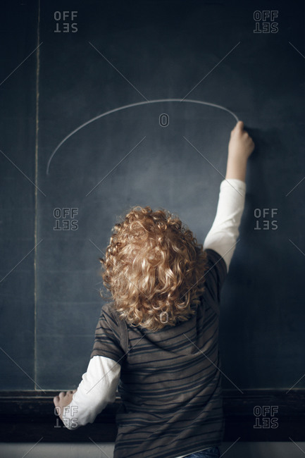 Boy drawing on a chalkboard in a school