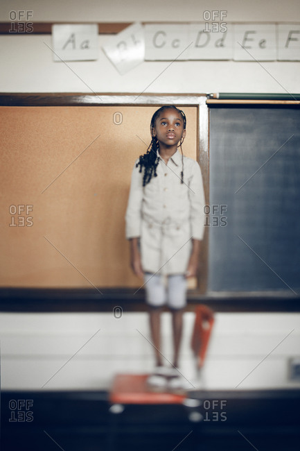Little girl standing on chair in a classroom