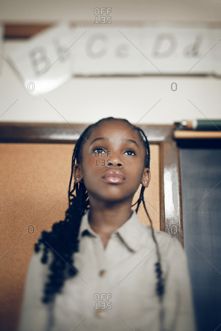 Little girl standing on a chair in a classroom