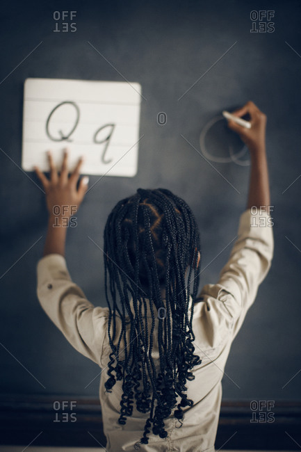 Girl practicing writing cursive letters on chalkboard