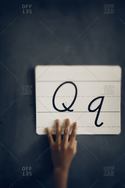 Girl's hand holding letters against chalkboard