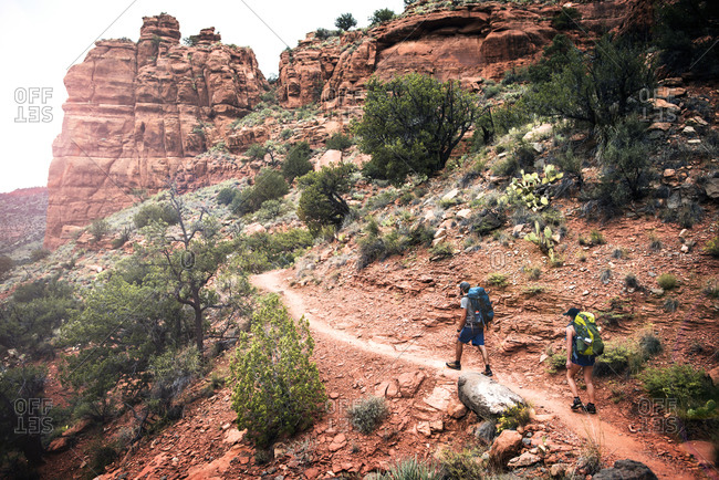 Couple hiking along trail in rocky mountain terrain