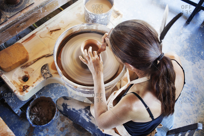 Woman shaping clay on a potter's wheel