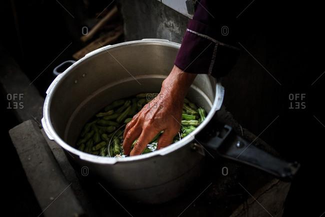 A woman cooks green beans in YingPanXu, Jiangxi, China