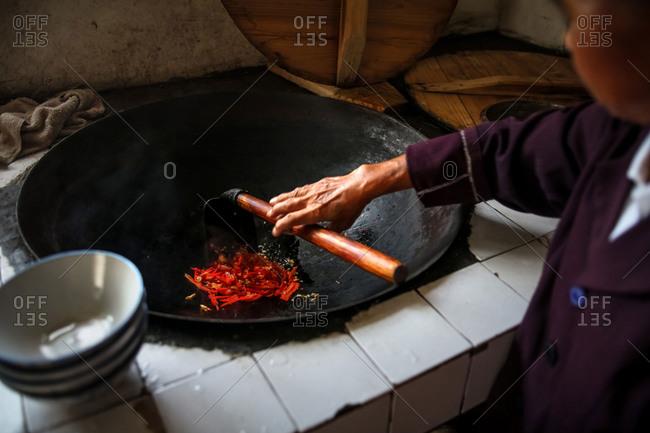 A woman cooks chili peppers in YingPanXu, Jiangxi, China