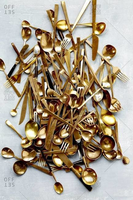 Pile of gold flatware on a blue background