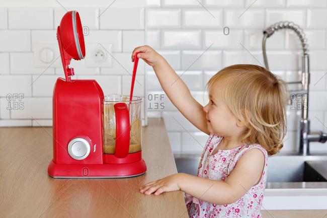 Little girl grabbing a spoon from a blender of homemade applesauce
