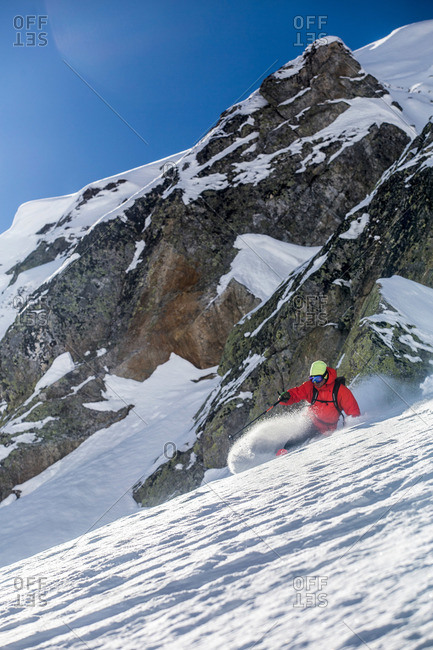 Man skiing a rocky steep mountain in winter