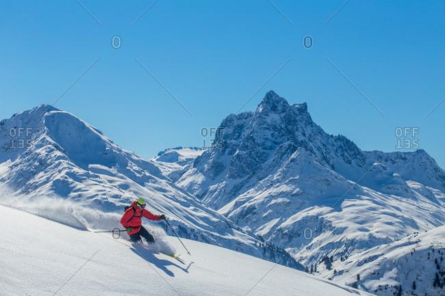 Man downhill skiing on powder in St. Anton, Austria