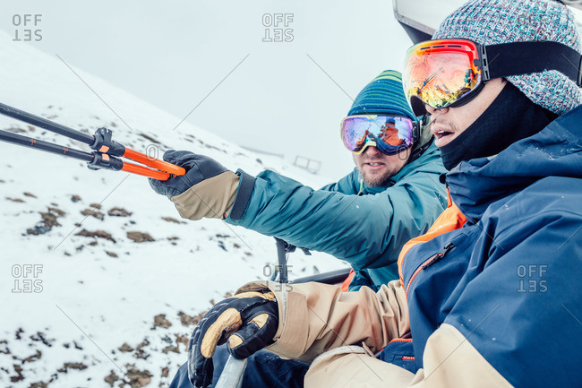 Two skiers ride a ski lift together