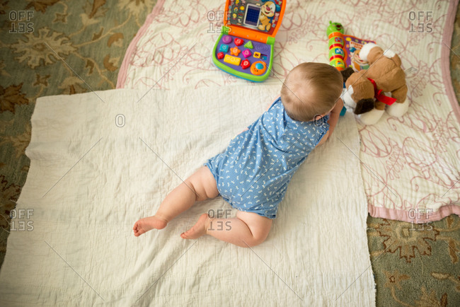 A baby plays on the floor with a stuffed animal