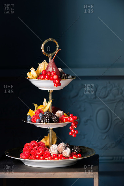 A three-tiered fruit tray in a blue room