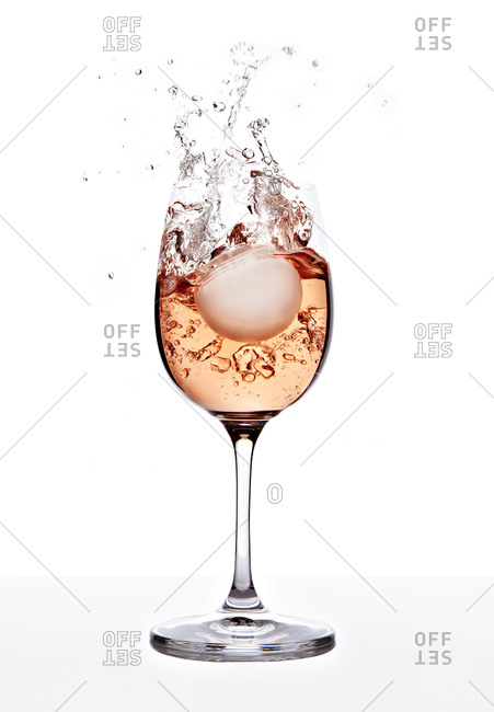 Round white ball splashing into a glass of wine