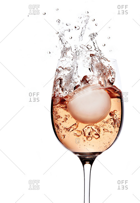 Ball splashing into a glass of rose wine