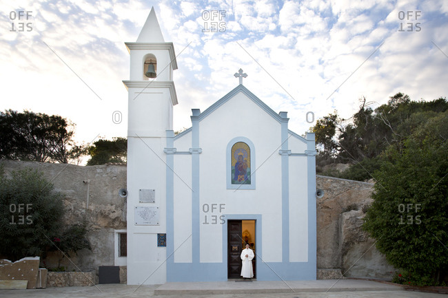 Lampedusa, Italy - November 22, 2013: Boy standing in the doorway of a Sicilian church