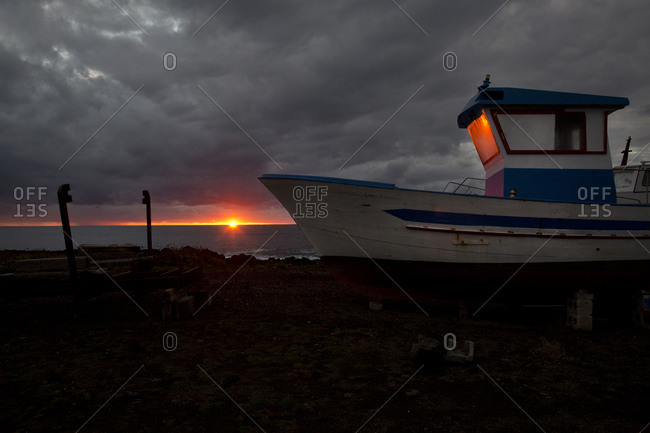 Boat on a dry rocky shore at sunset
