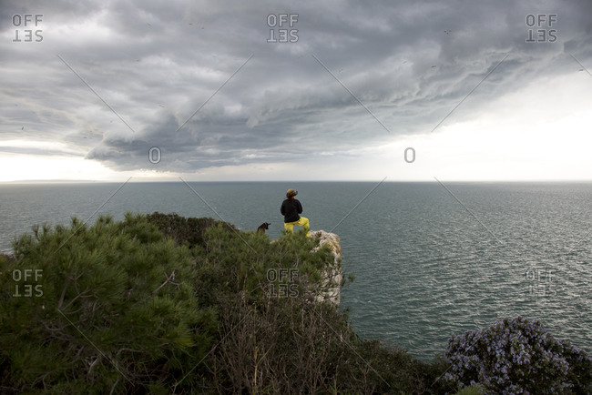 Woman standing on a bluff with her dog overlooking the Mediterranean Sea
