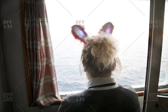 Girl with rabbit ears looking out a window at the sea