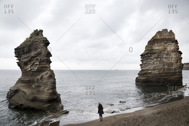 Woman standing on a beach between two large rock formations